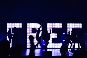 """people dancing in front of LED sign that says """"FREE"""""""