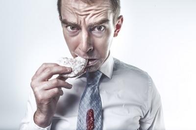 man looking worries eating a pastry