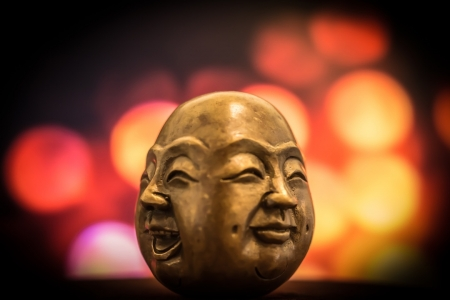 buddha head with happy and sad faces representing emotional Health
