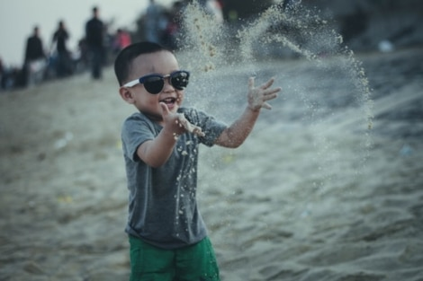 happy child throwing sand