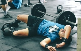 man laying on ground next to barbell