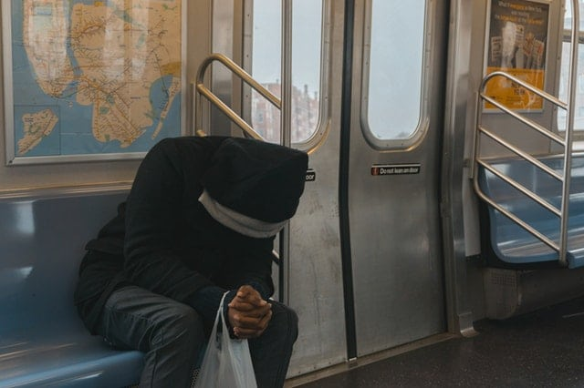 seated man bent over with hands clasped on subway train
