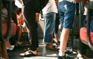 people's legs on a crowded subway train