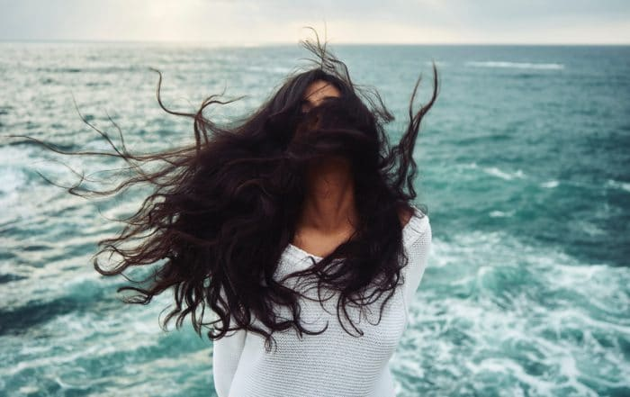 woman's hair blowing in wind by ocean