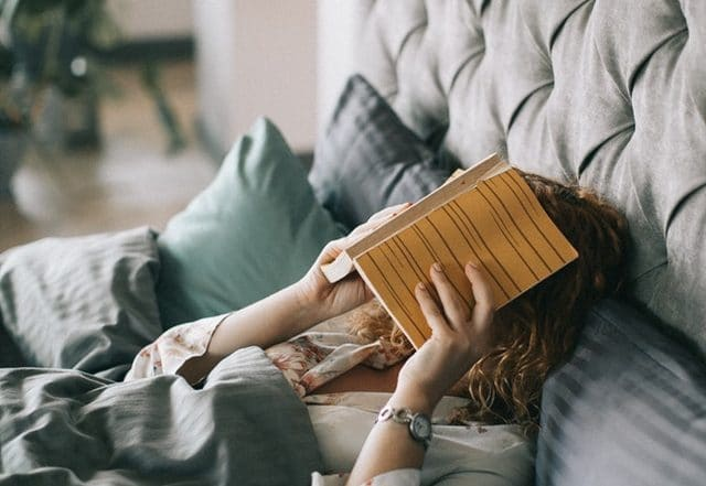woman in bed covering face with book