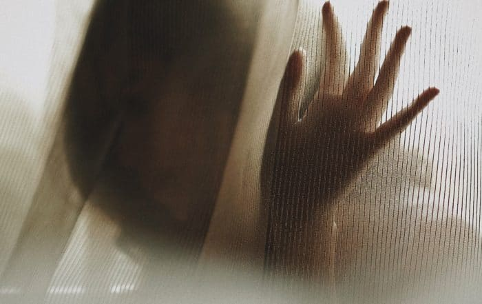 woman with hand on window